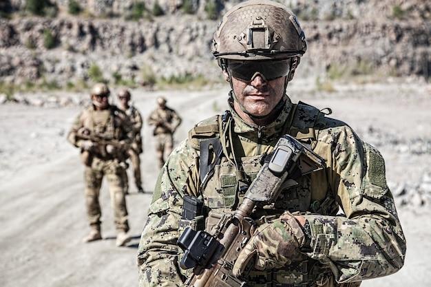 Equipo de escuadrones de fuerzas especiales en acción en el desierto entre las rocas
