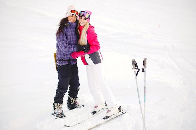 Equipo de esquí en manos de chicas. colores brillantes en la ropa de esquí. las chicas se divierten juntas.