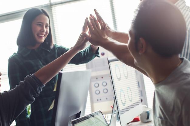 Equipo exitoso. gente asiática trabajando juntos en la oficina. y el pensamiento creativo son una lluvia de ideas.