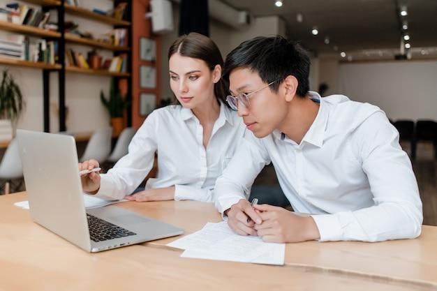 Equipo de exitosos empresarios diversos trabajan con laptop en la oficina