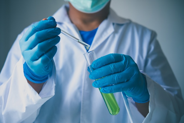 Equipo y experimentos científicos vertiendo aceite científico con tubo de ensayo verde haciendo investigación en laboratorio.
