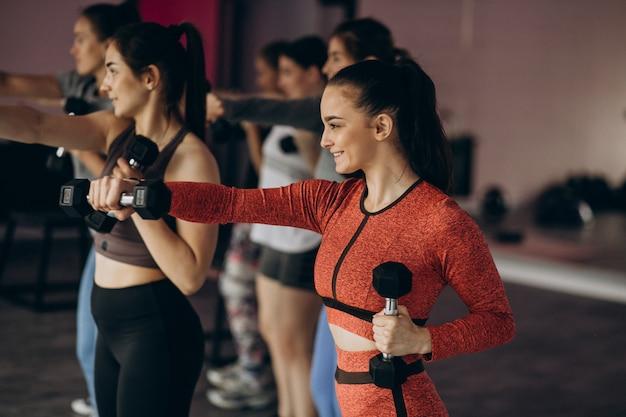 Equipo femenino que ejercita aeróbicos juntos en el gimnasio