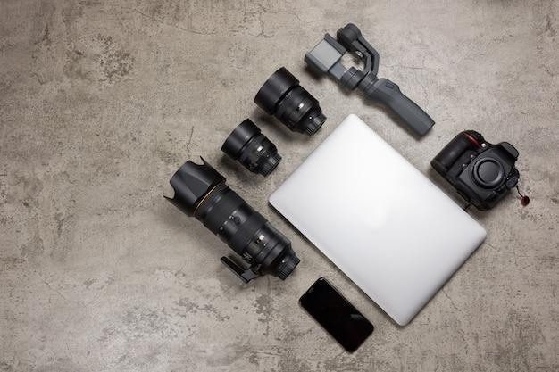 Equipo de fotografía para viajar sobre fondo de mortero desnudo, cámara dslr, lentes, computadora portátil, mouse y cardán.