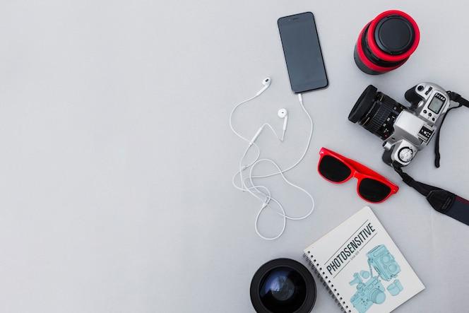 Equipo fotográfico con teléfono móvil sobre fondo gris