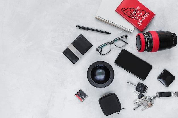 Equipo fotográfico, cuaderno de espiral y accesorios personales en el fondo