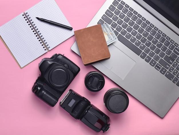 Equipo fotógrafo, portátil, monedero con dólares, cuaderno sobre un fondo rosa pastel. concepto independiente, trabajo de fotógrafo, objetos, vista superior, plano