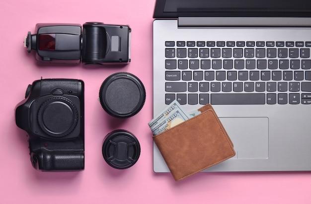 Equipo fotógrafo, portátil, monedero con dólares en un fondo rosa pastel. concepto independiente, trabajo de fotógrafo, objetos, vista superior, plano