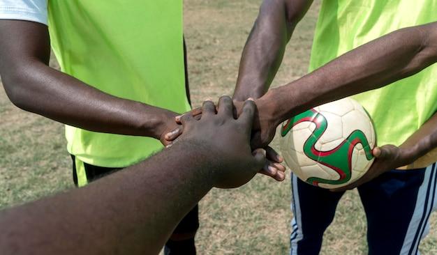 Equipo de fútbol en descanso haciendo apretón de manos