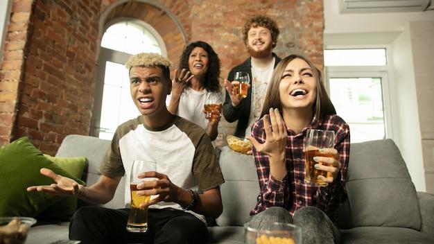 Equipo. gente emocionada viendo partido deportivo, campeonato en casa. grupo multiétnico de amigos, fanáticos animando al equipo deportivo favorito