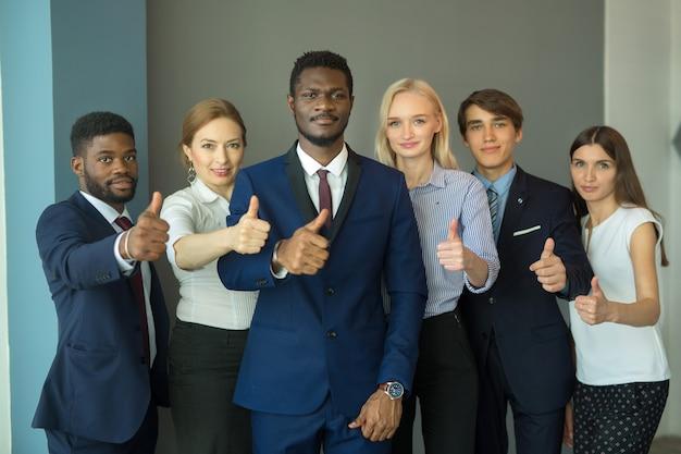 Equipo de gente joven hermosa en la oficina con gesto de mano