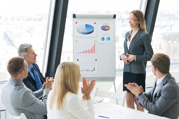 Equipo de gente de negocios en la presentación trabajando con gráficos y diarios en el rotafolio