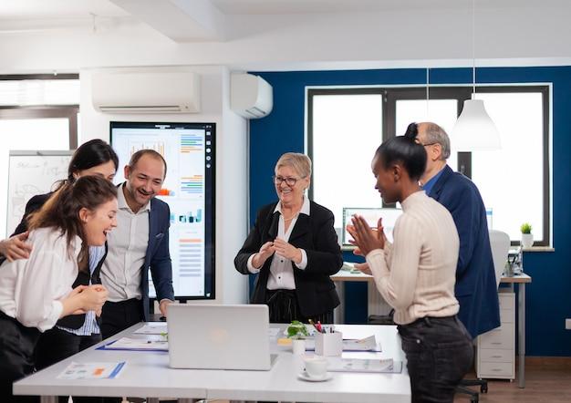Equipo de gestión aplaudiendo lleno de alegría en la sala de conferencias después de una buena formación