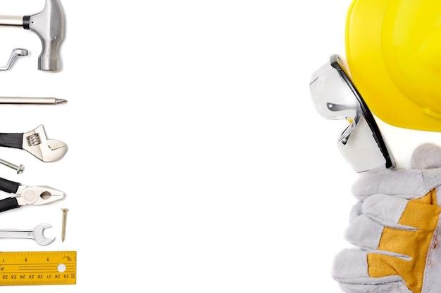 Equipo y herramientas de seguridad de construcción en el fondo blanco.