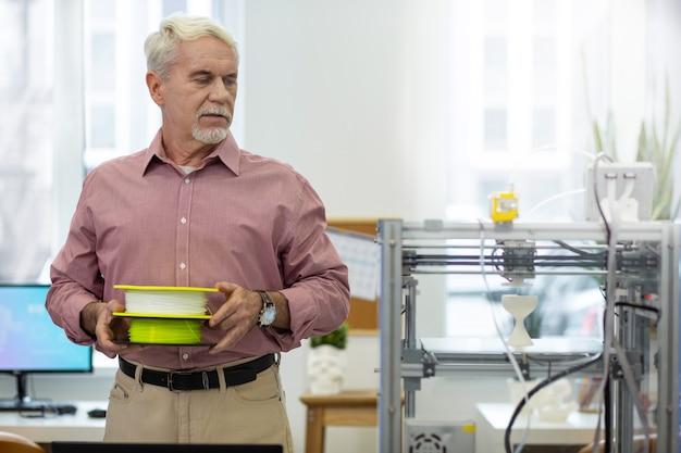 Equipo importante. hombre mayor encantador que trae carretes de filamento y está a punto de cambiarlos en una impresora 3d