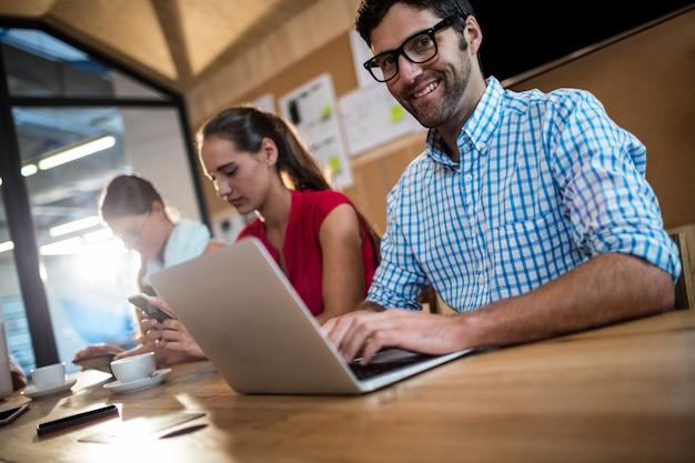 Equipo informal de negocios usando computadoras portátiles