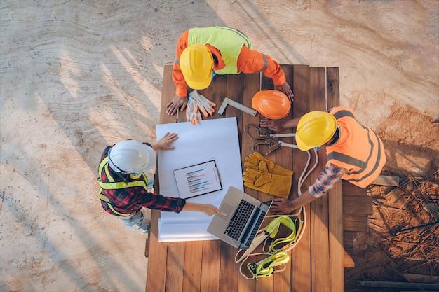 Equipo de ingenieros y arquitectos trabajando, reuniéndose, discutiendo, diseñando, planificando, midiendo el diseño de planos de construcción en el sitio de construcción, vista superior, concepto de construcción.