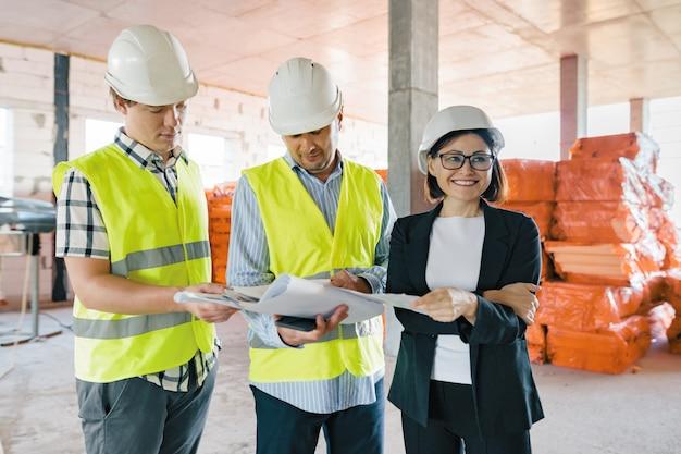 Equipo de ingenieros constructores en obra, leyendo planos