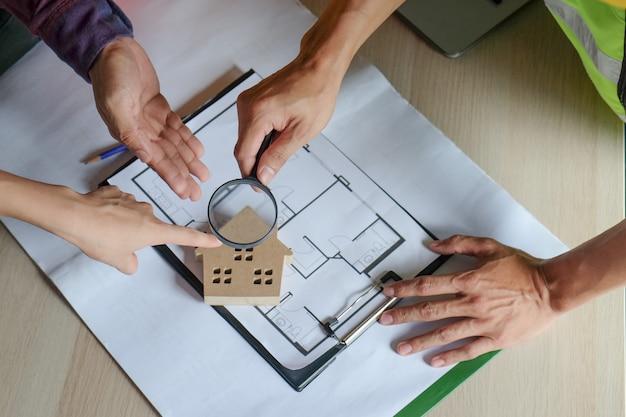 Equipo de ingenieros e inspectores inspeccionando y apuntando al modelo de la casa