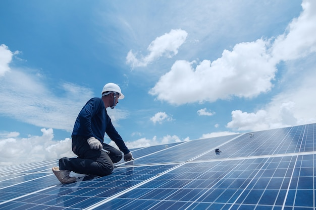 Equipo de ingenieros y electricistas intercambiando e instalando paneles solares