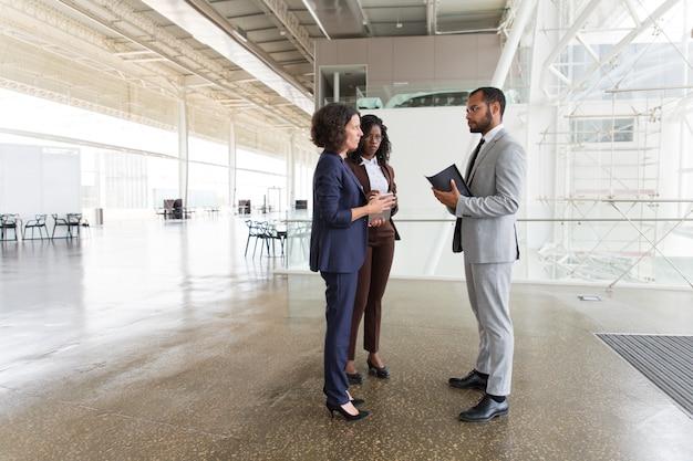 Equipo interracial discutiendo proyecto en pasillo de oficina