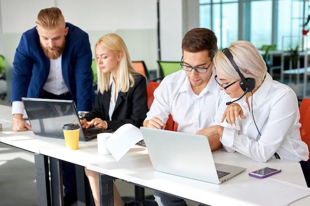 Equipo joven concentrado en el trabajo en la computadora portátil mientras el director cerca de ellos, se sientan juntos a la mesa