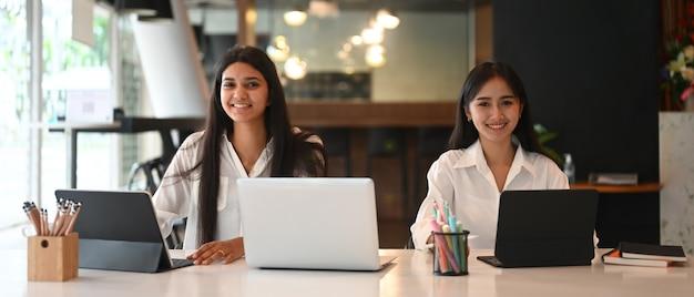 Equipo de joven diseñador gráfico trabajando junto con una computadora portátil y una mesa