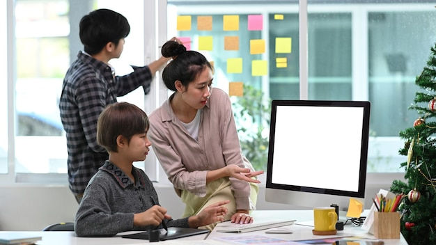 Equipo de jóvenes diseñadores intercambiando ideas y discutiendo un nuevo proyecto en el lugar de trabajo creativo