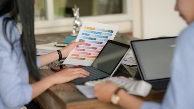 Equipo de jóvenes diseñadores profesionales escribiendo en tableta digital