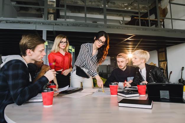 Equipo de jóvenes profesionales de negocios que utilizan tecnología en una reunión informal dedicada al diseño de arquitectos. estudiantes internacionales que aprenden juntos en la biblioteca universitaria. concepto de inicio exitoso