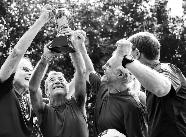 Equipo de jugadores de fútbol maduros ganando la copa