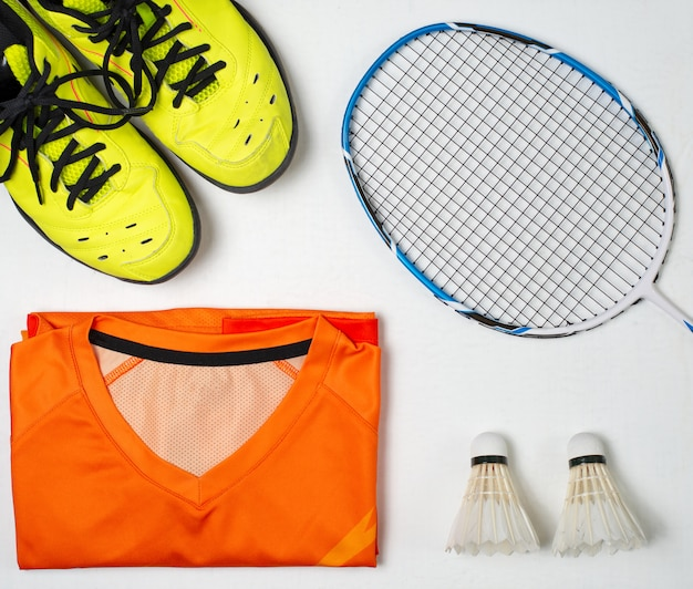 Equipo para jugar al bádminton, zapatos, camiseta deportiva, raqueta de bádminton, pelota de bádminton.