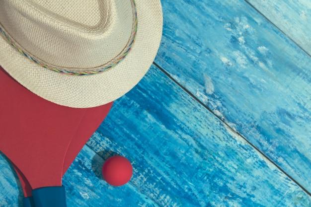 Equipo para jugar tenis de playa en la mesa de madera azul