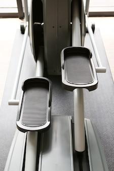 Equipo y máquinas en el gimnasio moderno de la sala de gimnasio