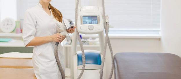 Equipo de masaje glp en un salón de belleza con un trabajador médico con equipo en sus manos.