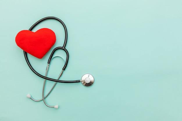 Equipo de medicina estetoscopio o fonendoscopio y corazón rojo aislado sobre fondo azul pastel de moda.