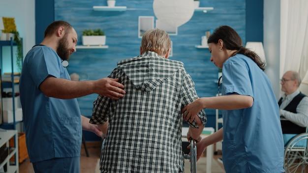 Equipo médico ayudando a la mujer mayor con discapacidad