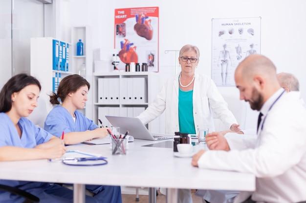 Equipo médico concentrado usando laptop juntos en la sala de reuniones del hospital. terapeuta experto de la clínica hablando con colegas sobre la enfermedad, profesional de la medicina