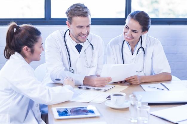 Equipo médico discutiendo en reunión en una sala de conferencias