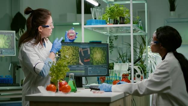 Equipo médico discutiendo sobre placa de petri con carne vegana analizando omg