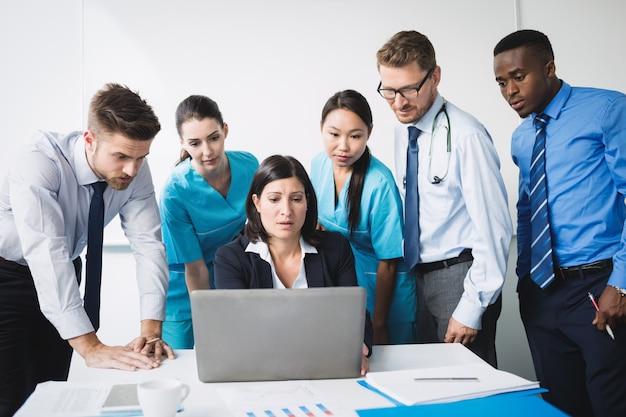 Equipo de médico discutiendo sobre portátil en reunión