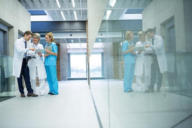 Equipo médico discutiendo sobre tableta digital en el corredor