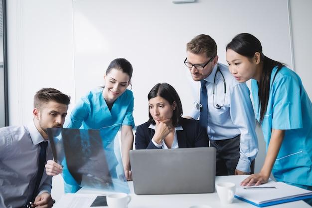 Equipo médico examinando un informe de rayos x.