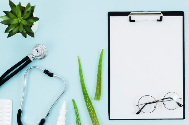 El equipo médico con hojas de aloe vera cerca del libro blanco en el portapapeles sobre fondo azul