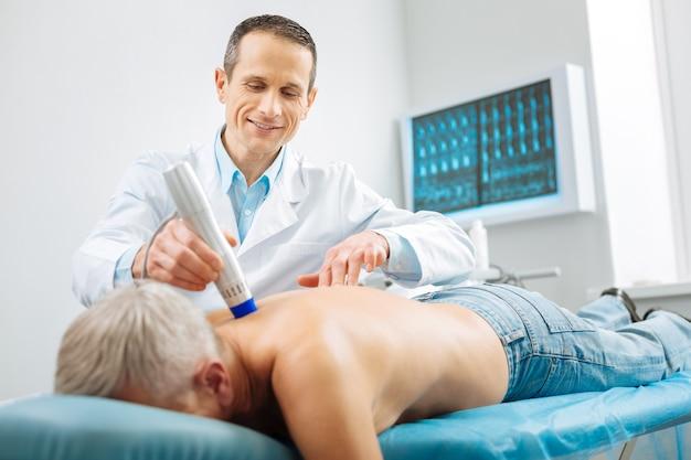 Equipo medico. médico guapo agradable profesional de pie cerca de su paciente y usando un dispositivo especial mientras hace un masaje