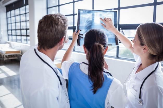 Equipo médico mirando rayos x juntos en el hospital