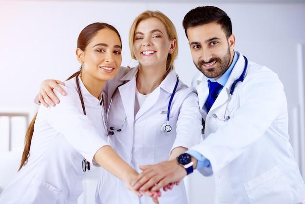 Equipo médico multirracial apilando las manos en el hospital