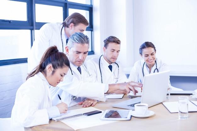 Equipo médico que mira en la computadora portátil y que tiene una discusión en la sala de conferencias