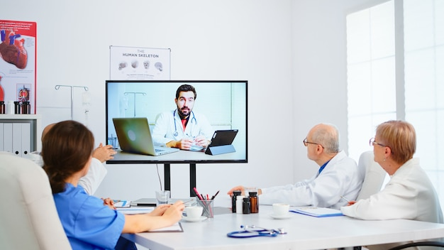 Equipo médico que realiza una conferencia en línea en la sala de juntas con un médico especialista y toma notas en el portapapeles. grupo de médicos discutiendo el diagnóstico sobre el tratamiento de pacientes mediante videollamada