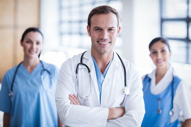 Equipo médico sonriente con los brazos cruzados en el pasillo