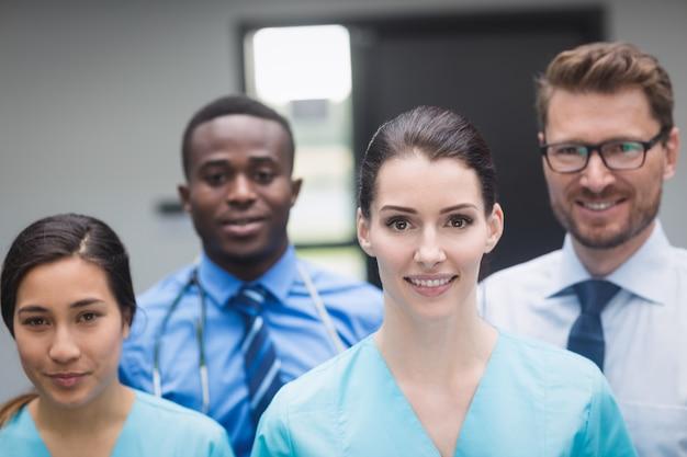 Equipo médico sonriente de pie juntos en el pasillo del hospital